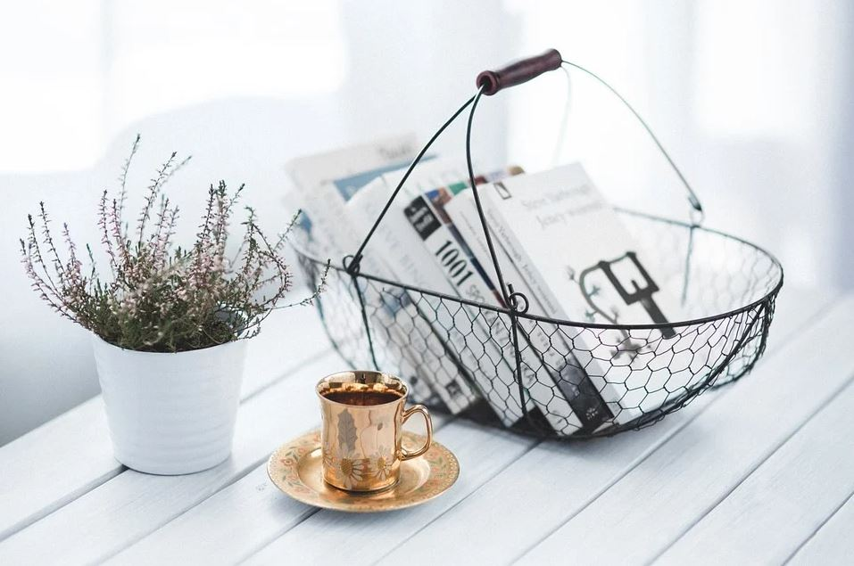 Books in a basket with gold coffee cup