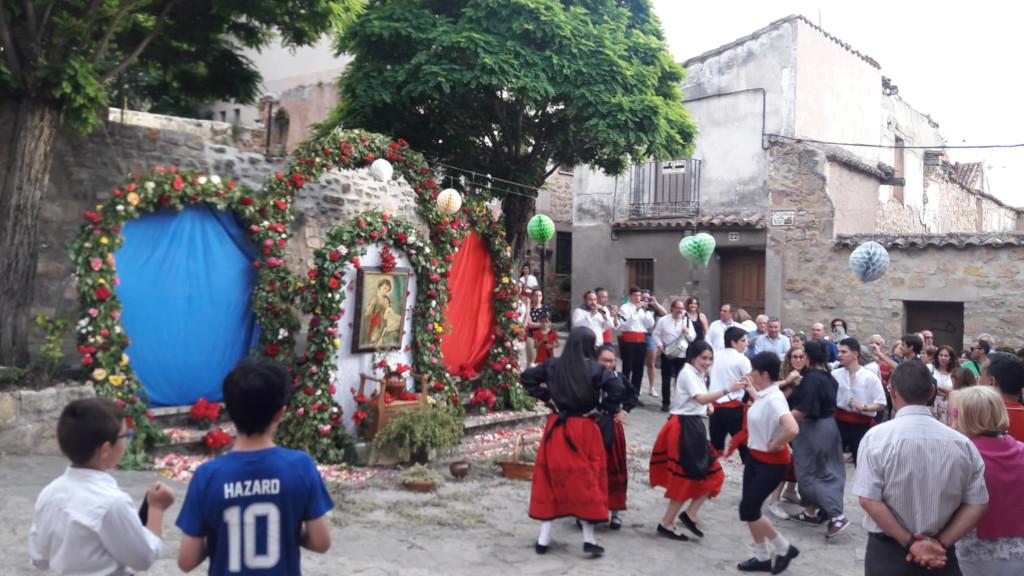 Escena en la plazuela de San Juan, con tres arcos floridos y jóvenes bailando jotas