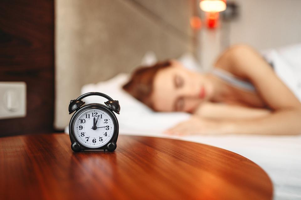 Girl sleeping with clock