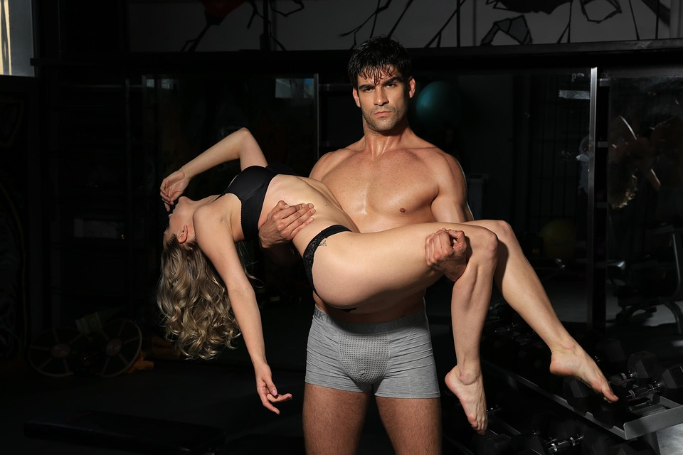 Sexy guy holding woman