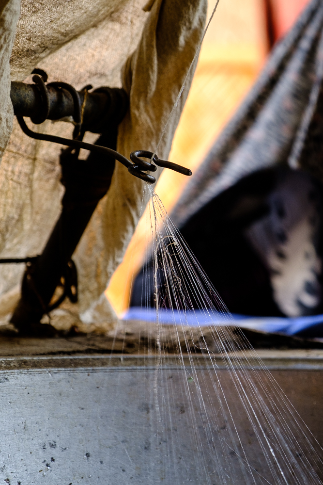 De zijderupsen worden chemisch gedood en daarna in warm water geweekt. Zo komt de zijde meer los en wordt ze op het spinnewiel tot draad gesponnen.