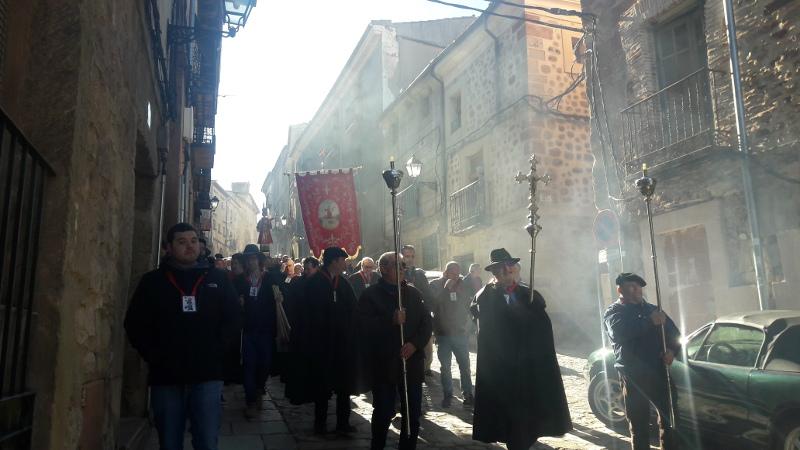 La comitiva de la procesión, presidida por su estandarte, descendiendo por la Calle Mayor