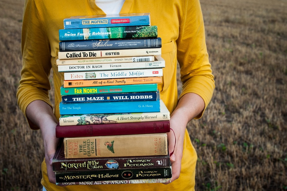 Girl with big pile of books