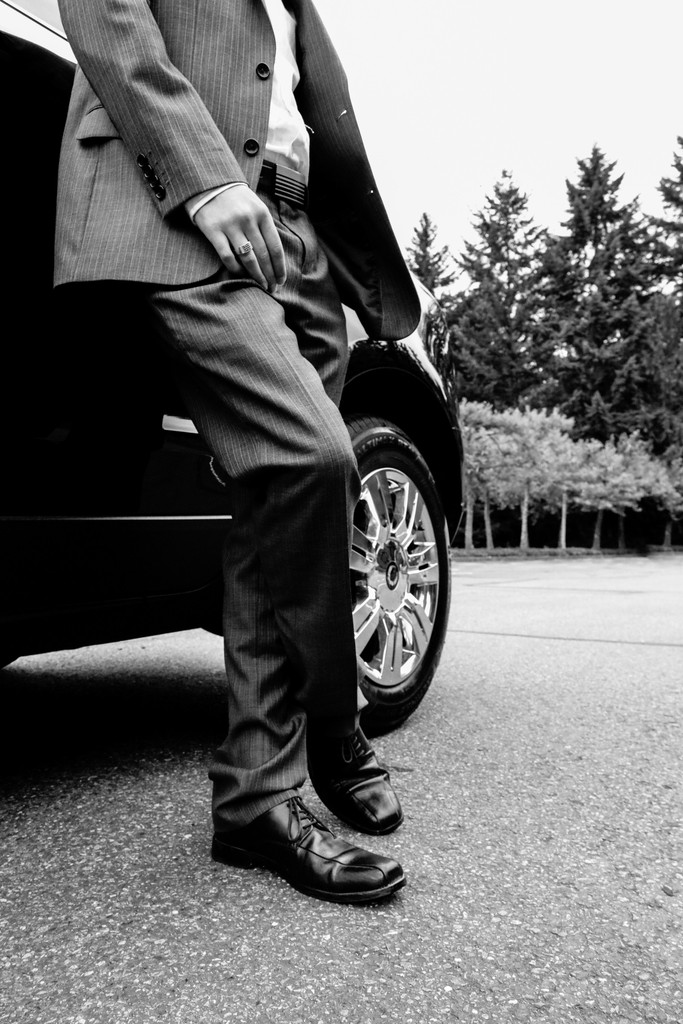 Man in suit leaning against a car