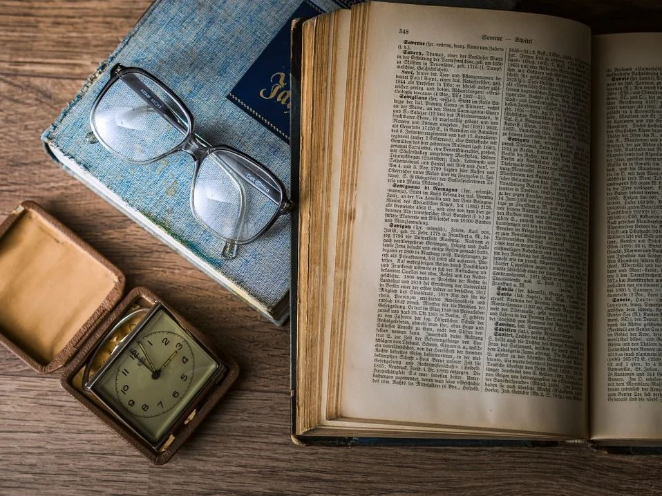 Old book with glasses and clock