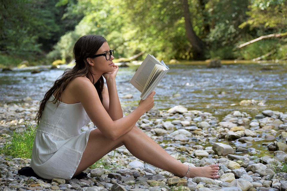 Woman reading by stream
