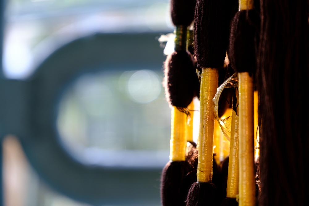 De patronen maken ze door een deel van de draden simpel met plakband af te plakken, en dan het hele boeltje in de gewenste kleurstof te doppen.