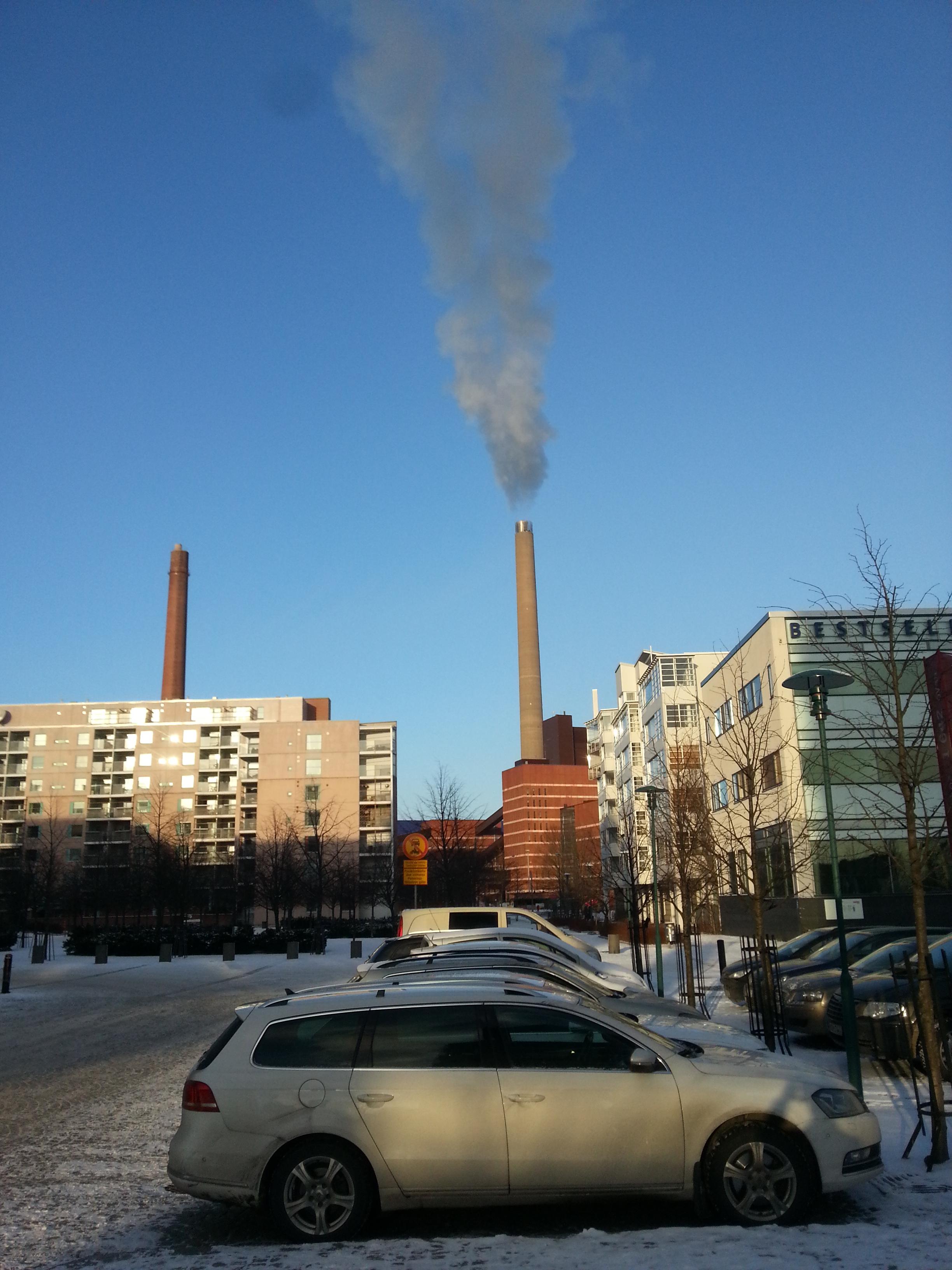 Hiilidioksidia tupruttava piippu ja henkilöautoja