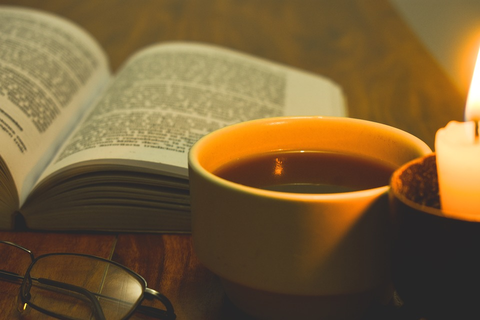 Book with coffee cup and candle