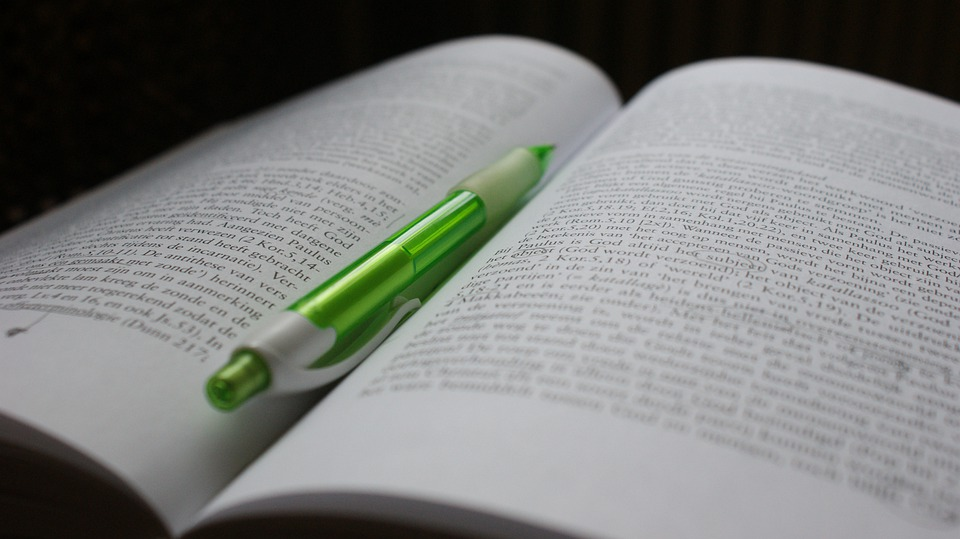 Open book with green pen