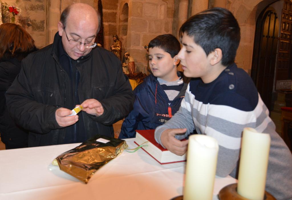 Don Jesús, acompañado por dos muchachos de la parroquia, recibe su regalo de Reyes